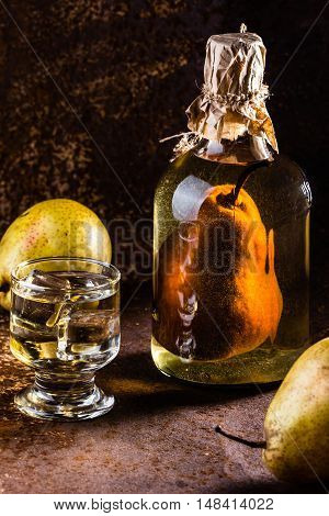 Traditional Chilean pear brandy with whole pear inside bottle. Aguardiente de pera. Bottle of pear aguardiente brandy and fresh pear on rustic dark background. Latin American drink