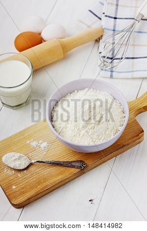 Flour in ceramic bowl with eggs and rolling pin on a white background.