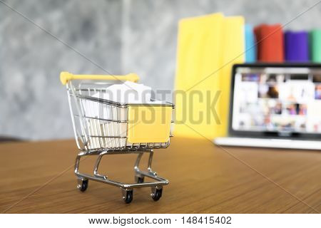 Business theme internet online shopping concept shopping delivery shopping cart carry shopping mail box and blur background of shopping bag and open laptop