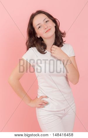 studio portrait of teenage girl on a pink background
