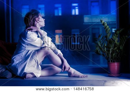 Half-dressed meditative girl in white shirt sits on window sill. Evening urban scene outside the window. Toned in blue colors