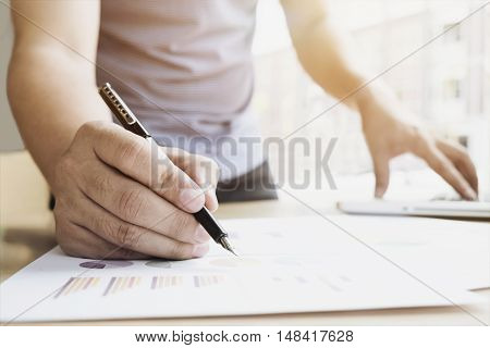 Businessman analize the marketing charts and graphs on desk.