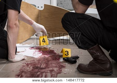 Two police officers at the scene looks at the traces of blood