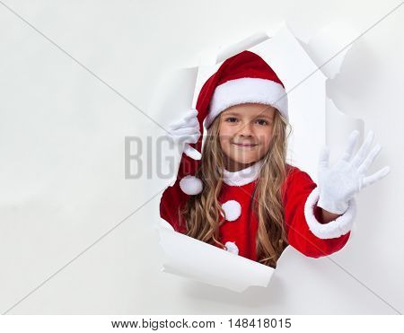 Little santa girl waving through hole in billboard - with white copy space