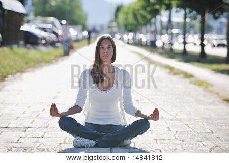 beautiful young woman meditating and exercise yoga in lotus position at street at beautiful sunny day with blured background