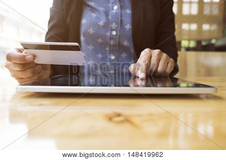 Woman using tablet to online shopping and pay by credit card. This picture is focus at woman's hand and use warm bright sunlight filter for feeling comfortable