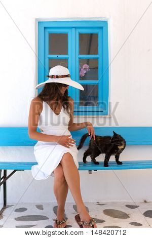 Young lady in white and a cat in front of a classic, Greek, blue window