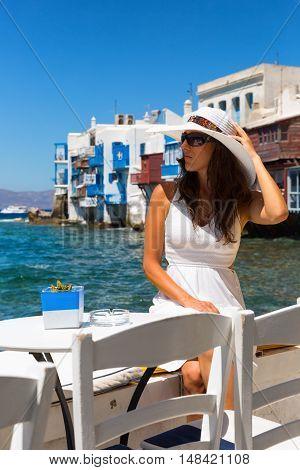 Woman in white dress sits in front of Little Venice in Mykonos, Greece