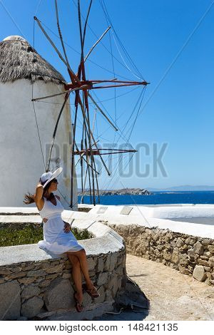 Woman in white dress sitting at the windmills at Mykonos town, Greece