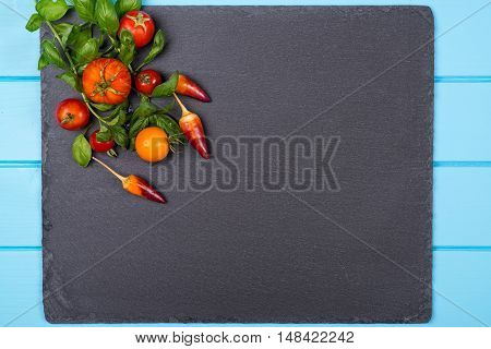 Fresh tomatoespepper and basil on black slate. Space for text.