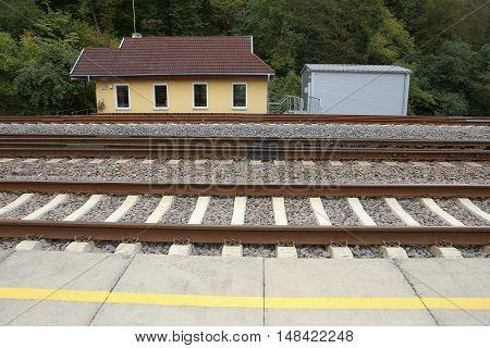 Small station near railroad. Rail Baltica railway station platform. yellow line.