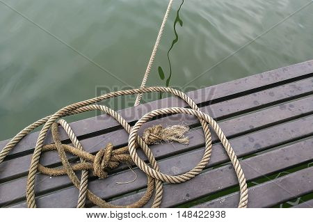 boat rope , rope knot on wood and water