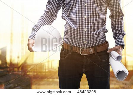 engineer holding construction helmet and rolls of blueprint on isolate white background with clipping mask