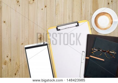 Top view of stuff office desktop and copy space. Analize data chart show on paper and tablet planner notebook glasses and coffee.