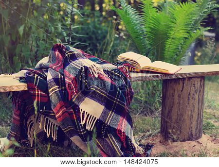 Woolen plaid and Open book at summer background