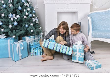 Woman Reads Wrapped Christmas Gift To Child Sitting Near Christmas Tree