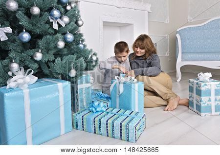 Boy With Mom In The Morning Near A Christmas Tree With Gifts