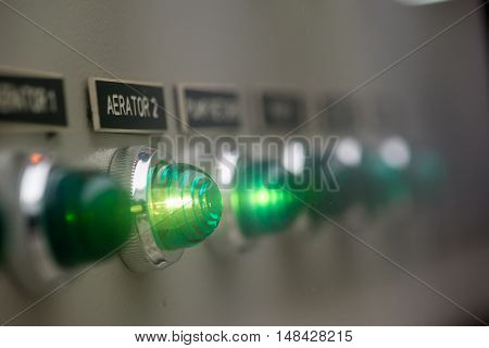 Close-up detail of green glowing lights on an industrial aerator control panel. Sewage management concept.