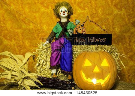 porcelain clown doll sitting on a bale of straw with jack-o-lantern and happy halloween sign with orange background