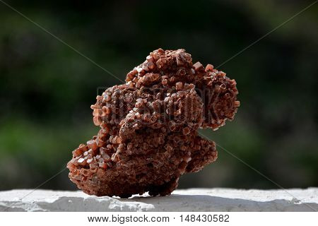 brown aragonite on white wall in sunlight with dark green background