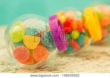 Three glass jars full of jellybeans on wooden table with blue background. Focus in the foreground