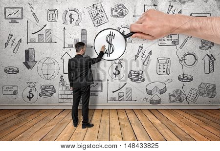 Back view of a businessman touching dollar sign enlarged by a magnifier in a man's hand on the background of a wall with business doodles. Management and administration.