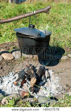 Camping fire and kettle with food
