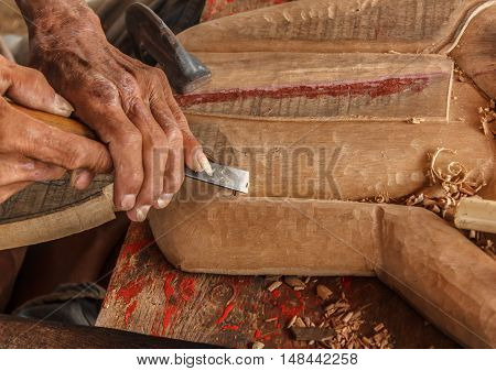 hands of the craftsman carve and tools of the wood carver