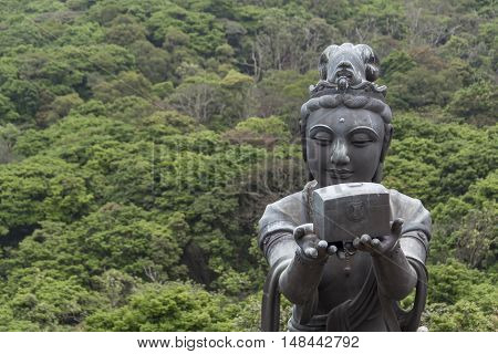 Buddhist statue making offerings to the Tian Tan Buddha in Hong Kong, against a background of lush trees