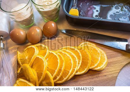 Cooking in the kitchen, a wooden board with a knife, sliced orange, flour in a glass