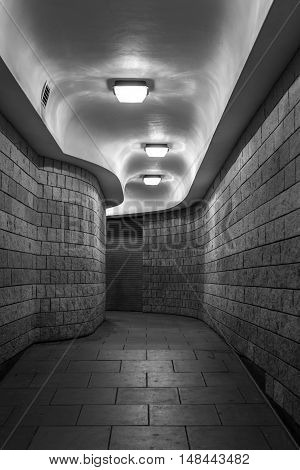 a curving pedestrian tunnel (subway) in the City of London, at night - black and white