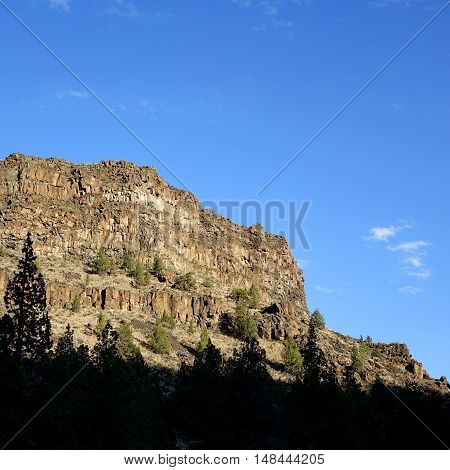 Towering Cliff with jagged rock cut away in the evening of a Central Oregon fall day.