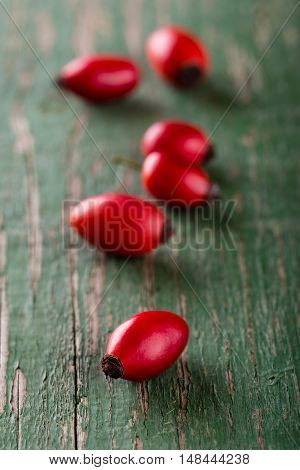Several Red Hips Placed In A Row On Green Wooden Board