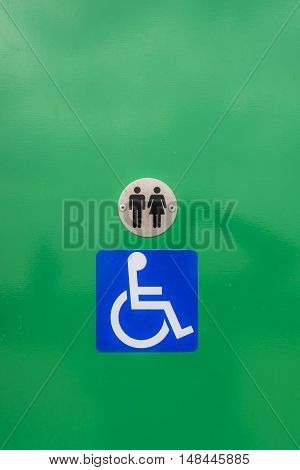 Disabled toilet sign, against a green background