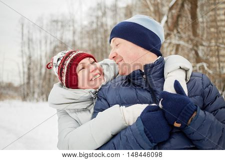 Half-length portrait of embracing happy smiling man and woman looking at each other in winter park.