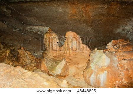 Underground cave with stalactites and stalagmites. Limestone karst formation on the walls of caves