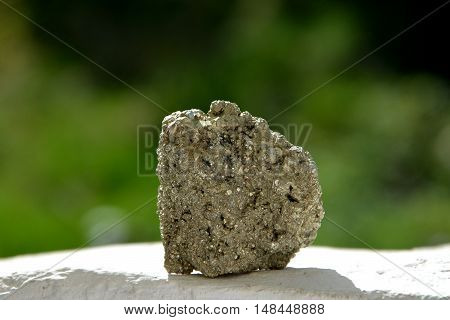 Golden Minerals Pyrite on a white wall against green background