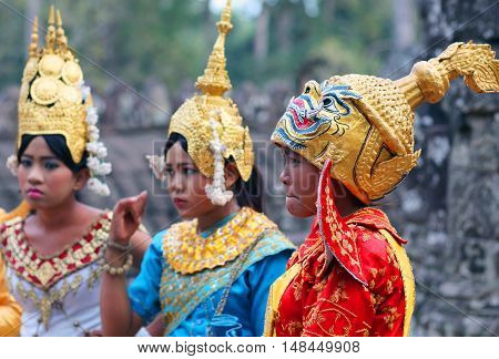 ANGKOR, CAMBODIA - JANUARY 7, 2013: Khmer children in traditional costume poses for a tourists in Angkor Wat, Cambodia