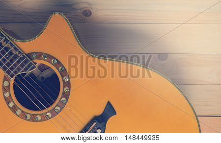 Half section of acoustic guitar on wood with copy space - toned
