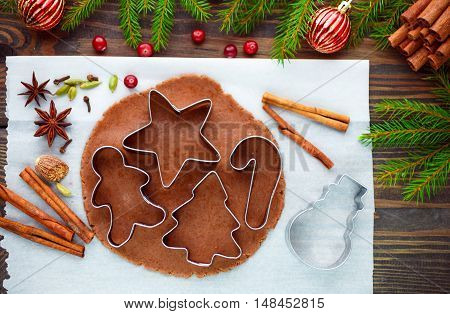 Gingerbread dough cookie cutters and spices on the table. Baking Christmas cookies. Cinnamon star anise cardamom nutmeg. Cranberry and pine branches