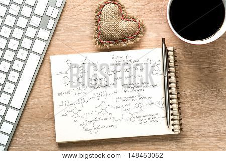 Keyboard notepad and coffee cup on wooden desk