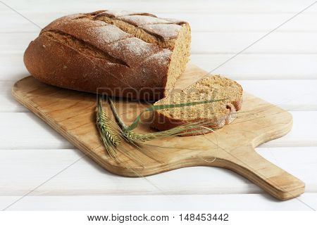 sliced bread lying on cutting wooden board decorated spikelet / traditional food