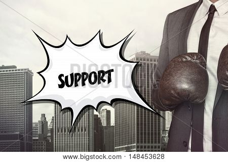Support text on speech bubble with businessman wearing boxing gloves