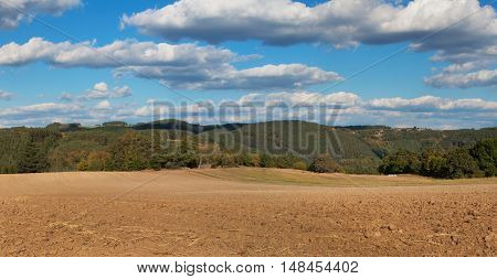 Freshly plowed field. Panorama of agricultural landscape. Autumn in agriculture. Blue sky and brown field.