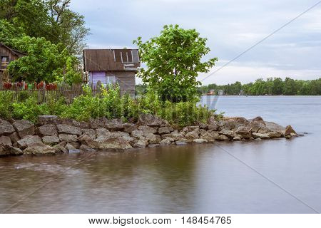 Stones on beach and huge rocks in calm water of Gulf of Vyborg. Evening calm in sea Bay Leningrad region Saint-Petersburg Russia