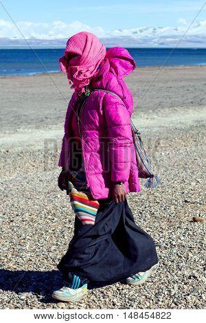 NGARI TIBET - MAY 7, 2013: Tibetan pilgrim in national clothes walking on the road across holy Manasarovar lake in Tibet Autonomus Region of China