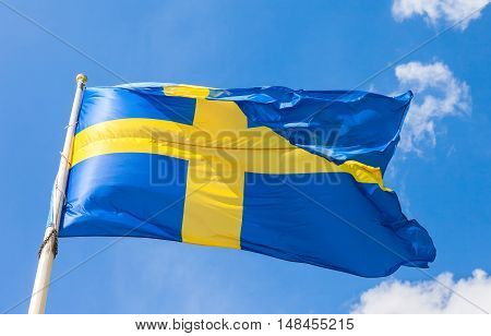 Swedish flag with yellow cross waving in the wind on a blue sky background