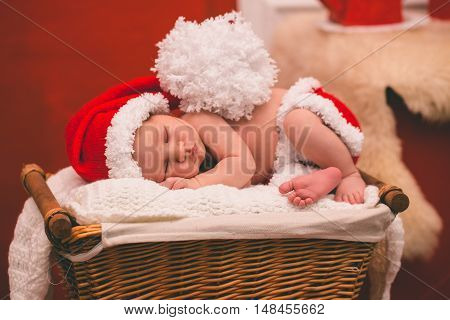 Portrait of newborn baby boy in Santa clothes sleeping in basket.