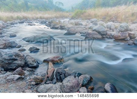 Beautiful Reshi River water flowing through stones and rocks at dawn Sikkim India. Reshi is one of the most famous rivers of Sikkim flowing through the state Shot under fog.