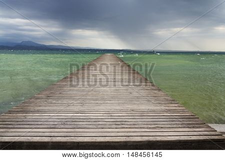 Wooden Pier With Waves On Lago Di Garda, Sirmione, Italy